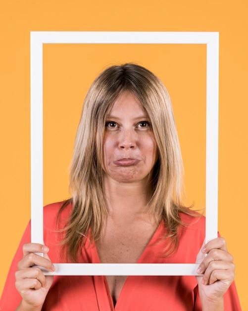 Mujer frunciendo los labios mientras sostiene el borde blanco marco de la imagen frente a su cara Foto gratis