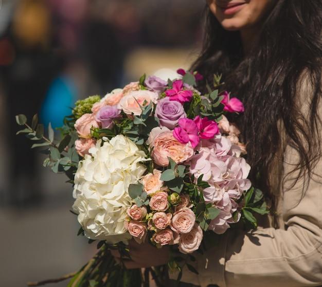 Mujer en gabardina con un ramo mixto de flores de invierno. Foto gratis