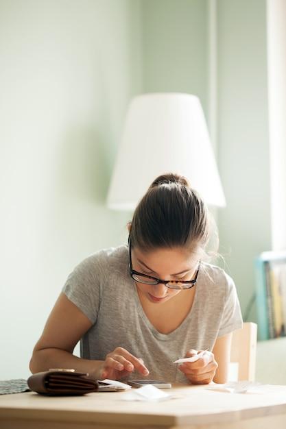 Mujer con gafas cuenta dinero en su teléfono Foto gratis