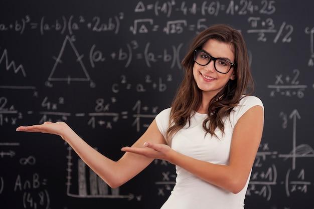 Mujer con gafas mostrando fórmulas matemáticas Foto gratis