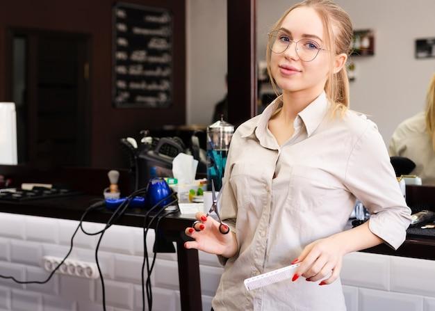 Mujer con gafas trabajando en una peluquería Foto Premium