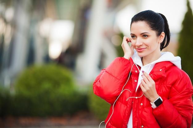 Mujer de gimnasio. chica bastante deportiva corriendo y escuchando música al aire libre. estilo de vida saludable en la gran ciudad Foto Premium