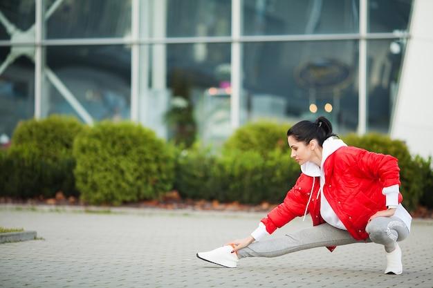 Mujer de gimnasio. mujer joven deportes que se extiende en la ciudad moderna. estilo de vida saludable en la gran ciudad Foto Premium