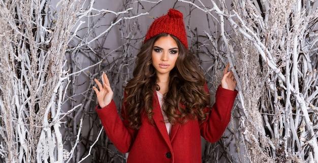 Mujer de glamour de belleza en el parque de invierno helado. hermosa mujer joven con sombrero de punto rojo, peinado ondulado increíble, labios carnosos y maquillaje brillante. Foto gratis