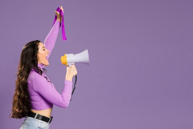 Mujer gritando en megáfono de pie de lado con espacio de copia Foto gratis
