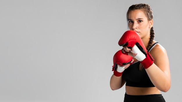 Mujer con guantes de box con copia espacio de fondo Foto gratis