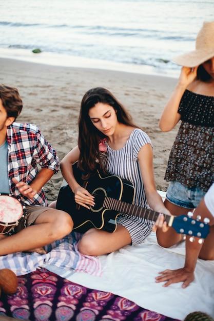Mujer con guitarra en la playa Foto gratis