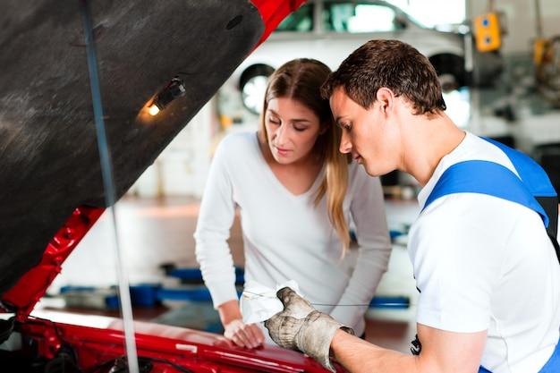 Mujer hablando con mecánico de automóviles en taller de reparación Foto Premium