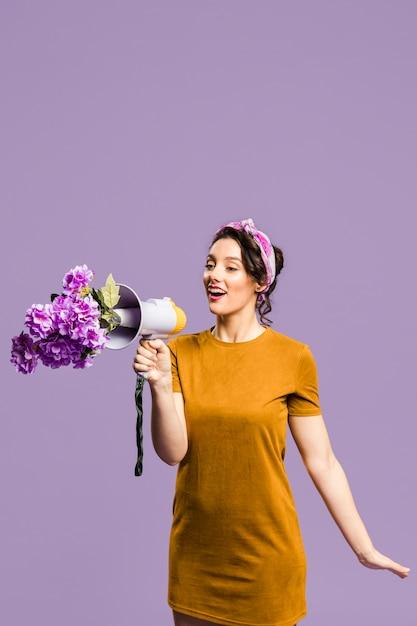Mujer hablando por el megáfono bloqueado por flores Foto gratis