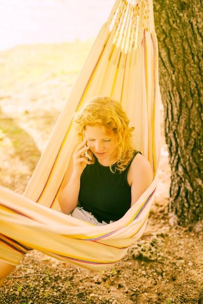 Mujer hablando por teléfono en hamaca Foto gratis