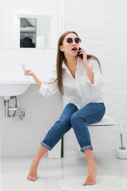 Mujer hablando por teléfono mientras está sentado en el inodoro Foto Premium