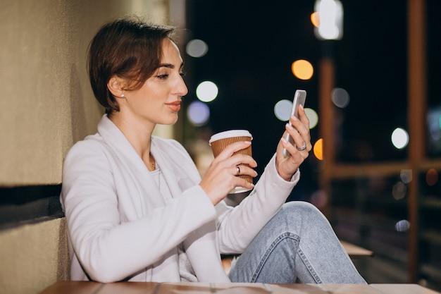 Mujer hablando por teléfono y tomando café afuera en la calle por la noche Foto gratis