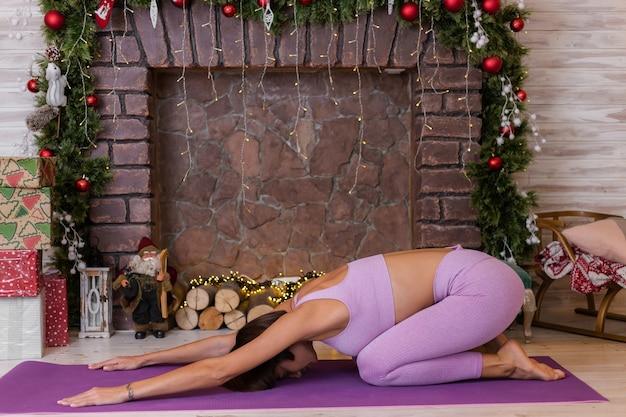 La mujer hace yoga en casa, fondo de navidad de año nuevo. Foto gratis