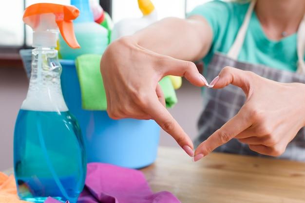 Mujer haciendo corazón con sus dedos delante de productos de limpieza Foto gratis