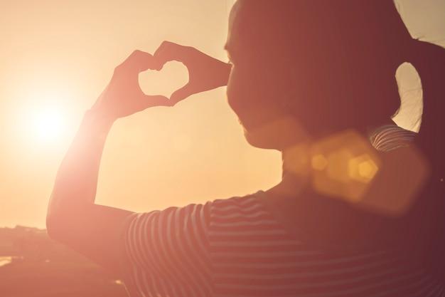 Mujer haciendo un corazón con sus manos Foto gratis