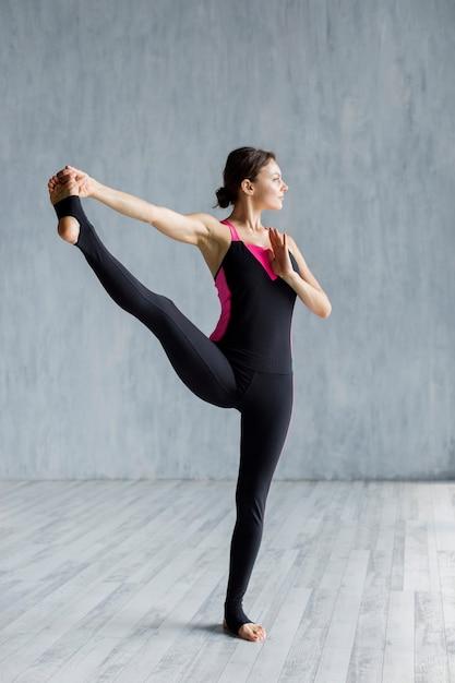 Mujer haciendo un ejercicio de estiramiento para piernas Foto gratis