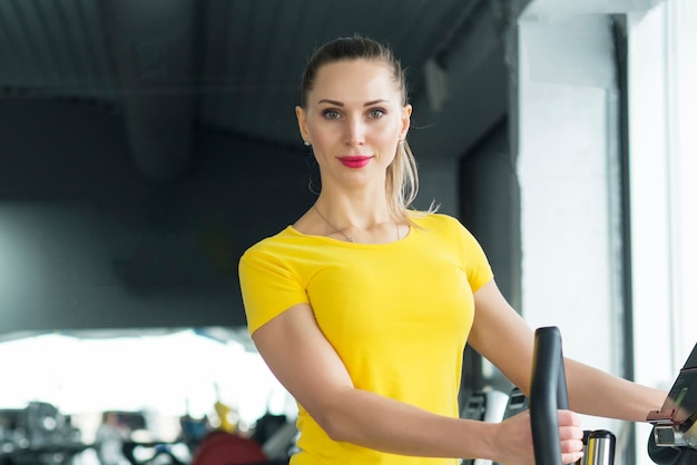 Mujer haciendo ejercicio en el gimnasio en un entrenador elíptico entrenamiento cardiovascular Foto Premium