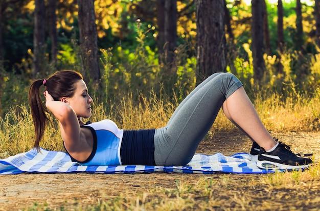 Mujer haciendo ejercicios de abdominales en el bosque
