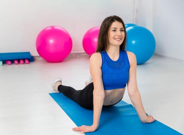 Mujer haciendo ejercicios en estera Foto gratis