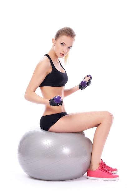 Mujer haciendo ejercicios con mancuernas en pelota de fitness Foto gratis