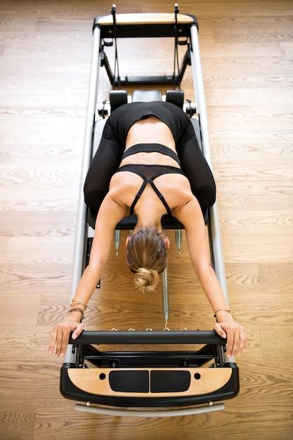 Mujer haciendo estiramiento de pilates en la cama de reformador Foto Premium