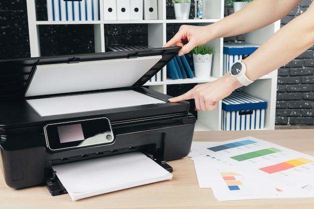 Mujer haciendo fotocopias con copiadora en la oficina Foto Premium