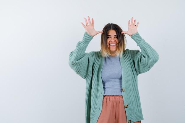 Mujer haciendo gesto de orejas en ropa casual y con aspecto divertido. vista frontal. Foto gratis