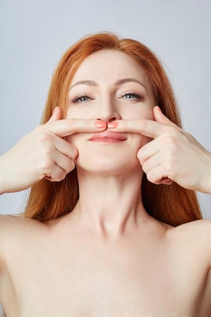 Mujer haciendo masaje facial, gimnasia, líneas de masaje y boca plástica, ojos y nariz. técnica de masaje contra arrugas y rejuvenecimiento de la piel. , abr Foto Premium