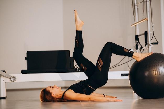 Mujer haciendo pilates con una pelota Foto gratis