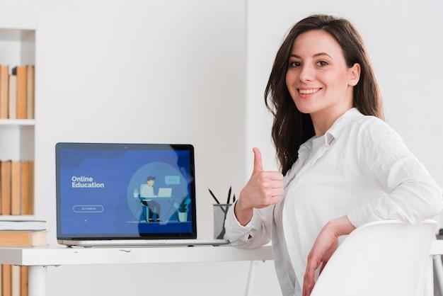 Mujer haciendo pulgares arriba gesto concepto de e-learning Foto gratis
