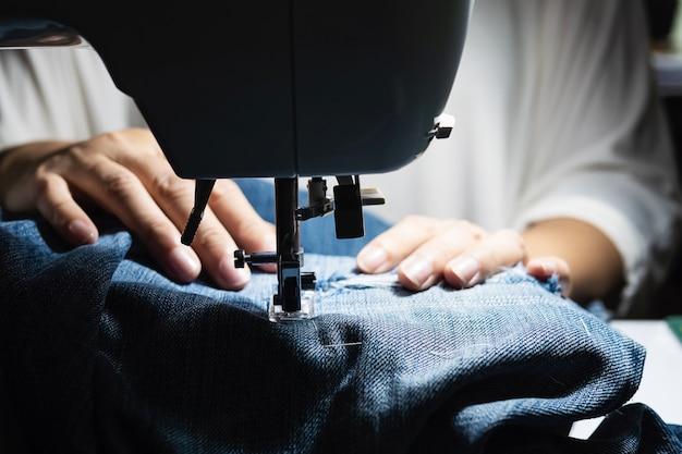 Mujer haciendo remiendo de jeans usando la máquina de coser - concepto de costura de bricolaje casero Foto gratis