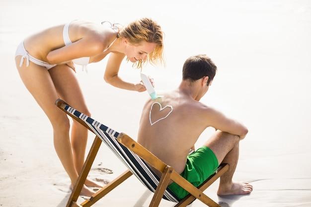 Mujer haciendo un símbolo de corazón en la espalda del hombre mientras aplica una loción de protección solar Foto Premium