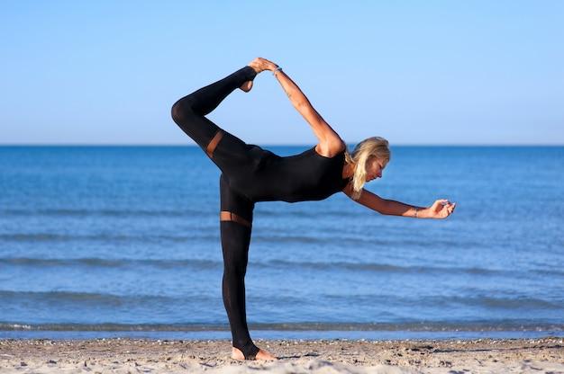 Mujer haciendo yoga asanas en la playa Foto Premium