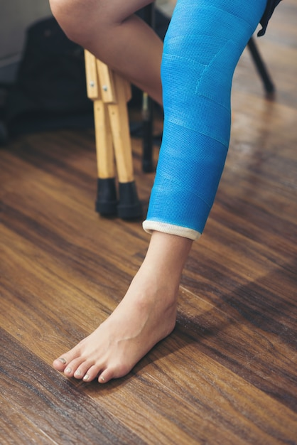Mujer herida con férula de pierna sentada y muletas de madera en el hospital Foto Premium