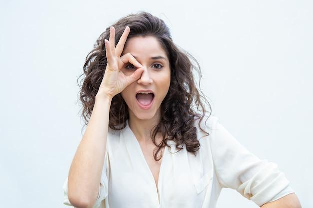 Mujer hermosa alegre con la boca abierta aplicando la mano al ojo Foto gratis