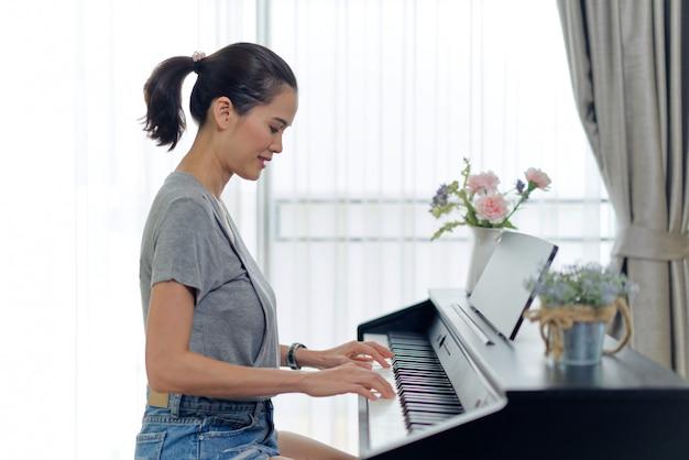 Mujer hermosa asiática que juega el piano electrónico en casa. Foto Premium