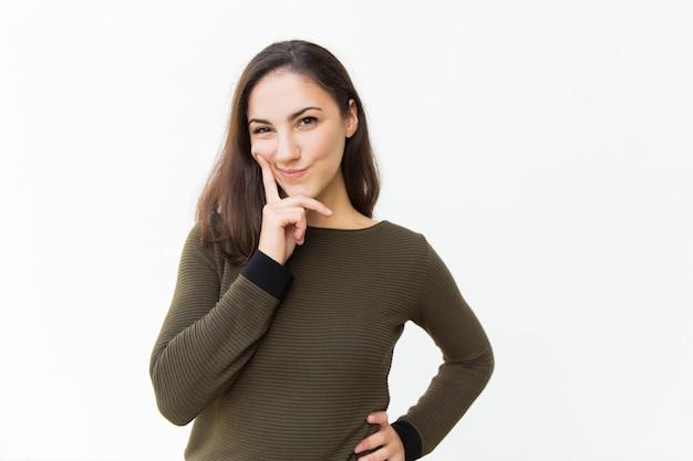 Mujer hermosa astuta pensativa que toca la barbilla Foto gratis