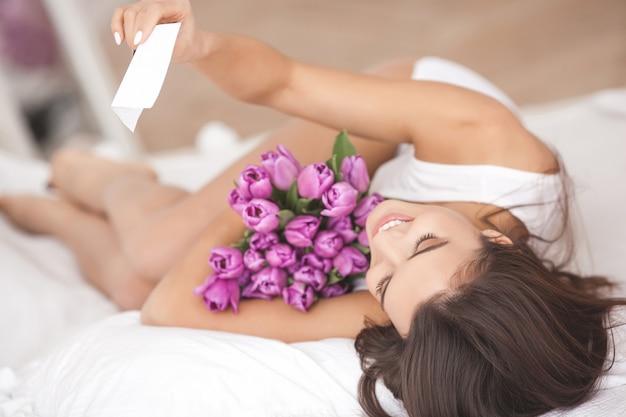 Mujer hermosa en la cama que sostiene las flores y que lee una nota. niña sonriendo. mujer alegre con tulipanes Foto Premium