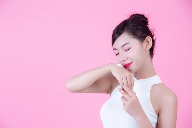 Mujer hermosa con crema en la piel en un fondo rosado. Foto gratis