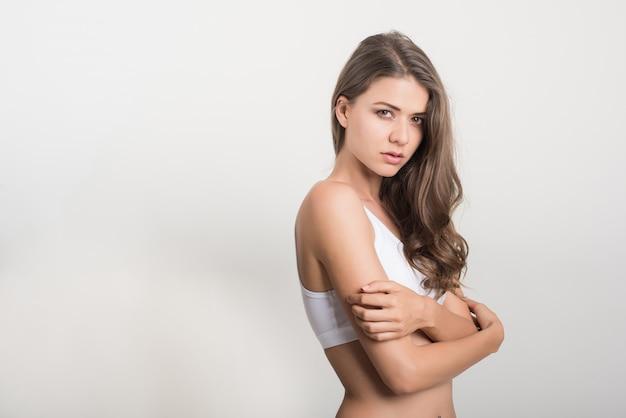 Mujer hermosa con el cuerpo sano en el fondo blanco Foto gratis