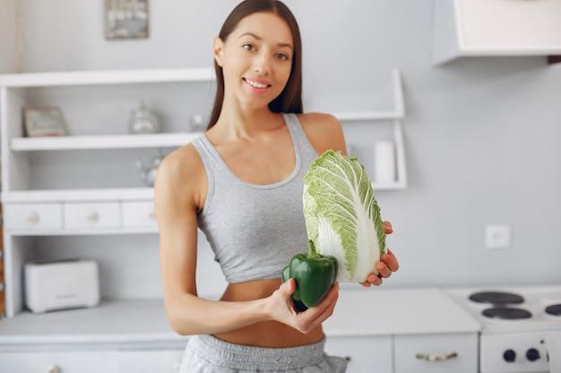 Mujer hermosa y deportiva en una cocina con verduras Foto gratis