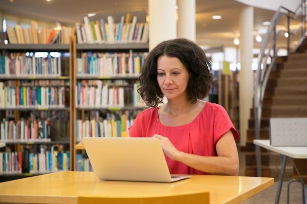 Mujer hermosa enfocada que mira la computadora portátil mientras está sentado en la mesa Foto gratis