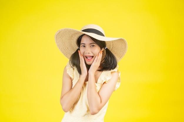 Una mujer hermosa y feliz con un gran sombrero que muestra alegría en un amarillo. Foto gratis