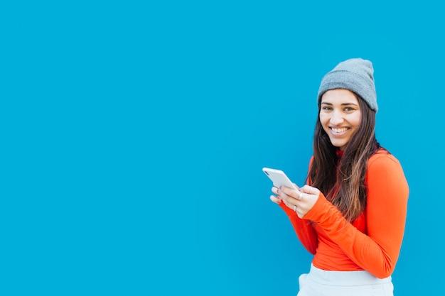 Mujer hermosa feliz que sostiene el teléfono móvil contra fondo azul Foto gratis