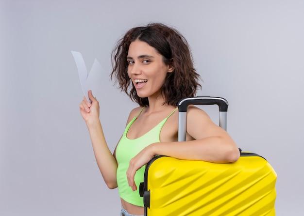 Mujer hermosa joven alegre del viajero que sostiene los billetes de avión y la maleta en la pared blanca aislada Foto gratis