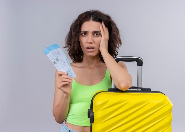 Mujer hermosa joven ansiosa del viajero que sostiene los billetes de avión y la maleta en la pared blanca aislada Foto gratis