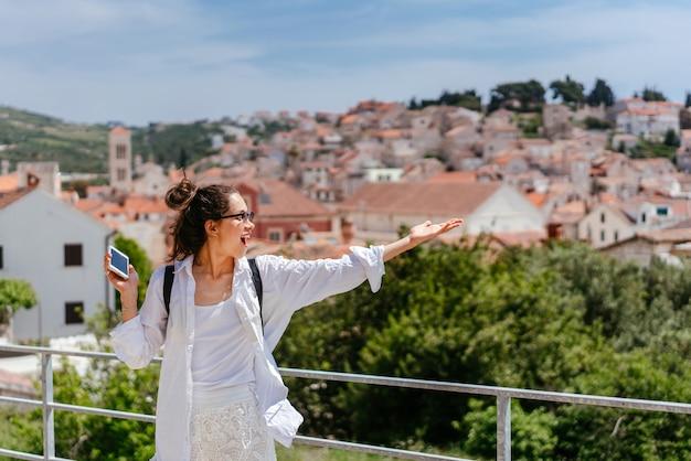 Mujer hermosa joven en un balcón con vistas a un pequeño pueblo en croacia Foto gratis