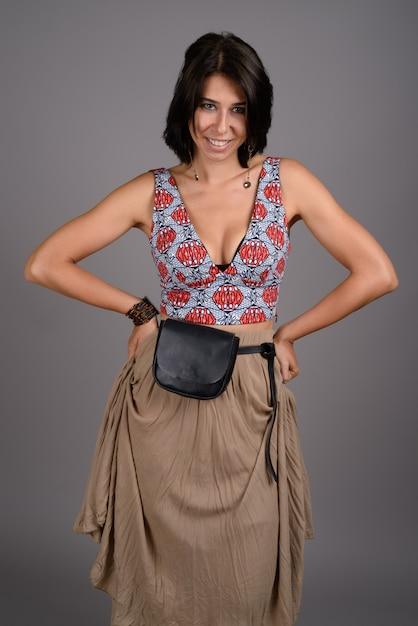 Mujer hermosa joven contra fondo gris Foto Premium