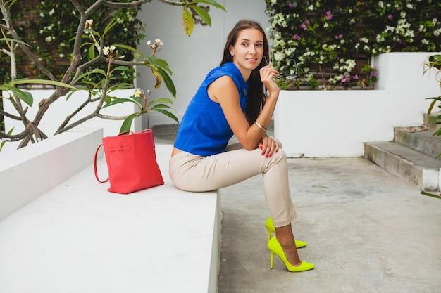 Mujer hermosa joven con estilo, tendencia de la moda de verano, blusa azul, bolso rojo, gafas, resort de villa tropical, vacaciones, piernas largas y delgadas coquetas, pantalones, zapatos amarillos, tacones Foto gratis