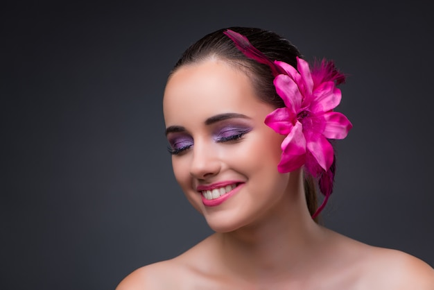 Mujer hermosa joven con la flor de la orquídea Foto Premium